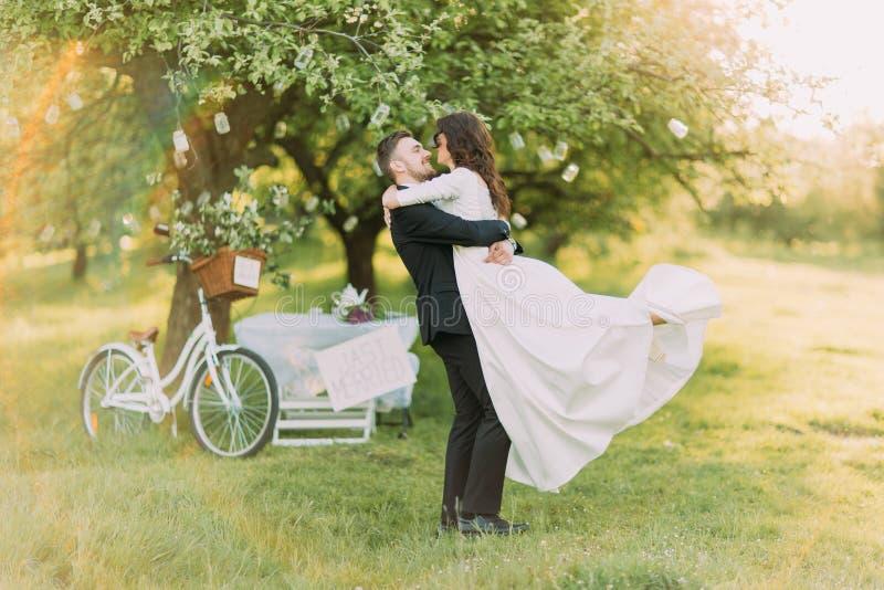Den lyckliga precis gift pardansen på gräsmatta i grönt soligt parkerar Dekorerat träd för cykel nära på bakgrund fotografering för bildbyråer