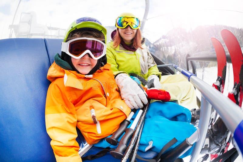 Den lyckliga pysen med mamman, berg skidar stolelevatorn royaltyfri foto