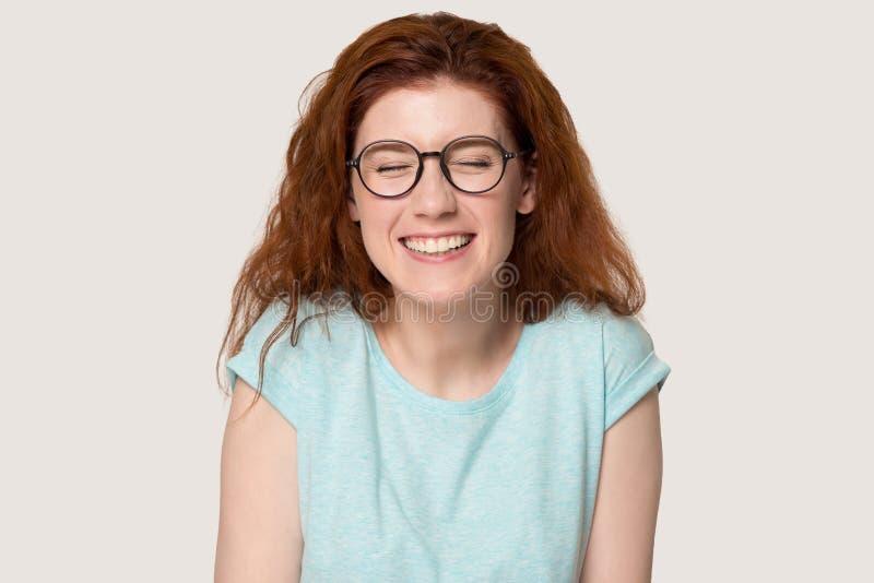 Den lyckliga rödhåriga flickan i exponeringsglas skrattar på det roliga skämtet fotografering för bildbyråer