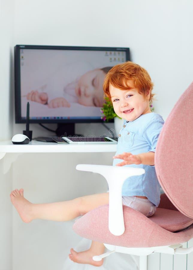Den lyckliga rödhåriga mannen som lilla barnet behandla som ett barn pojken, sitter i regeringsställning stol på arbetsplatsen royaltyfria bilder