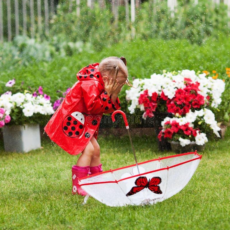 Den lyckliga roliga nätta lilla flickan i röd regnrock med paraplyet som in går, parkerar sommar royaltyfri bild