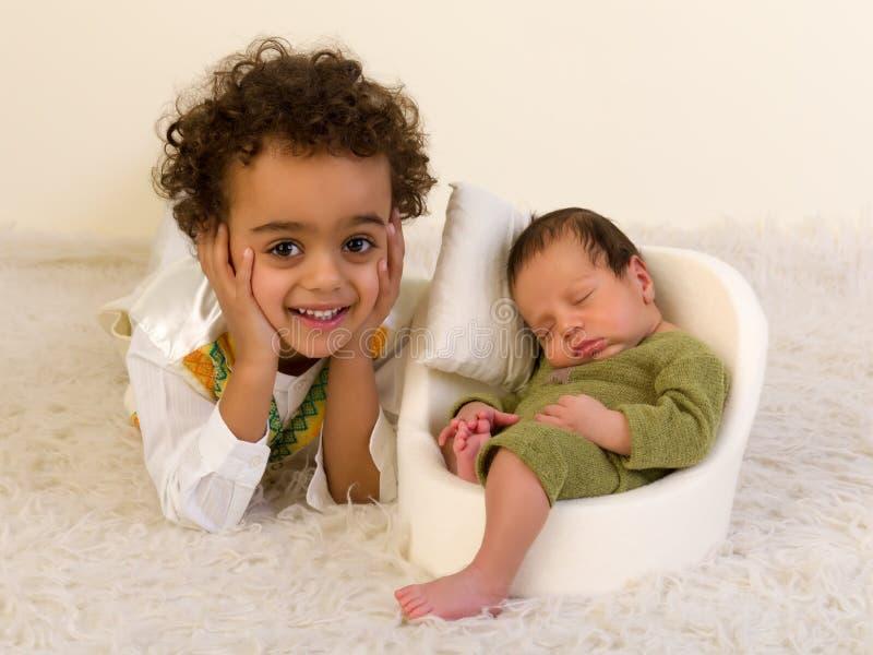 Den lyckliga siblingen med nyfött behandla som ett barn arkivbild