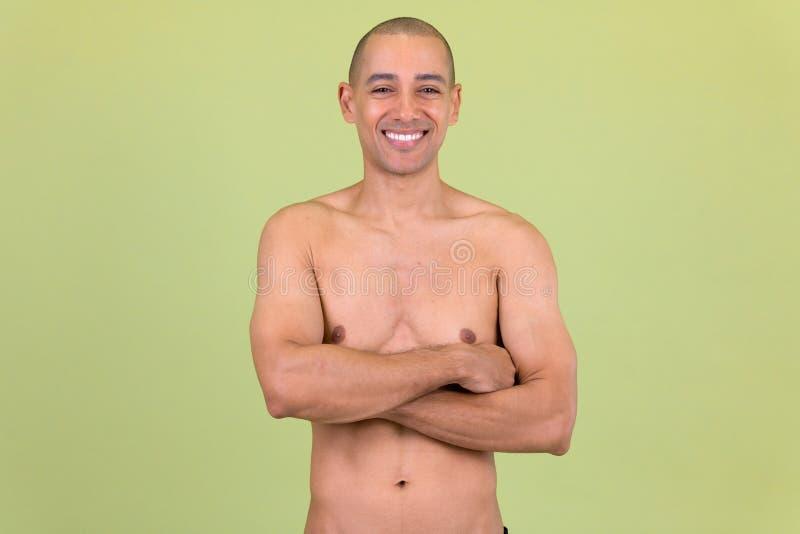 Den lyckliga skalliga mång- etniska mannen som ler med armar, korsade shirtless fotografering för bildbyråer