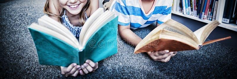 Den lyckliga skolan lurar att ligga på golv och läsning en bok i arkiv royaltyfria foton