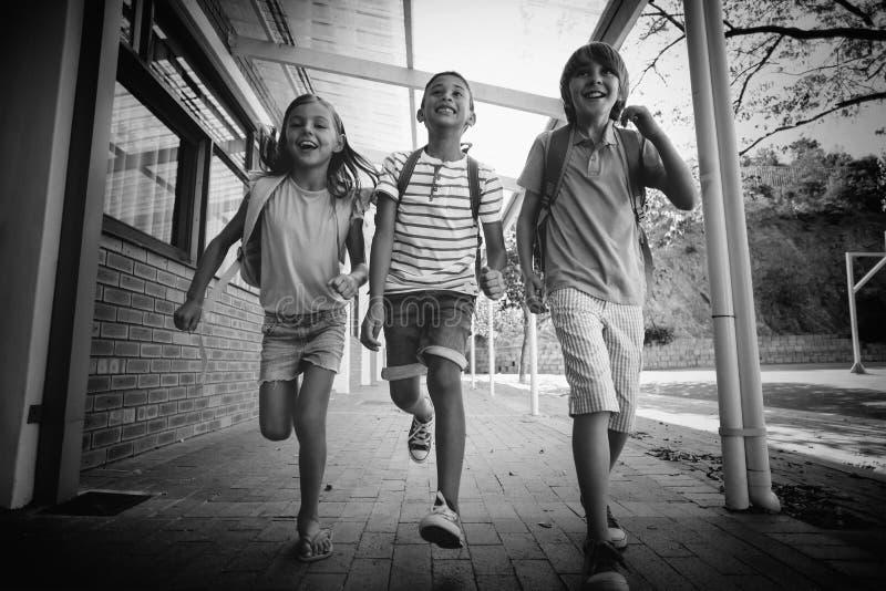 Den lyckliga skolan lurar spring i korridor royaltyfri foto