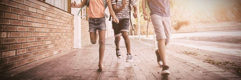 Den lyckliga skolan lurar spring i korridor fotografering för bildbyråer