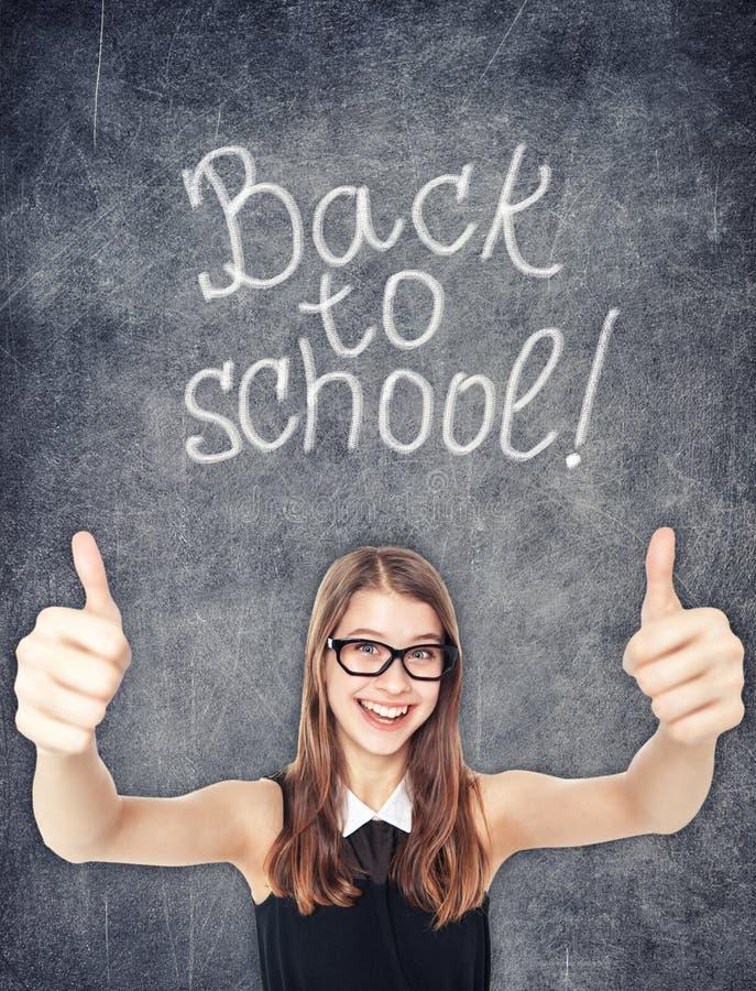 Den lyckliga skolflickavisningen tummar upp på svart tavlabakgrunden royaltyfri bild