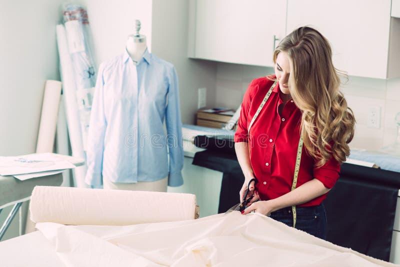 Den lyckliga skräddarekvinnan klippte stycktyg som arbetar i atelierstudio royaltyfri bild