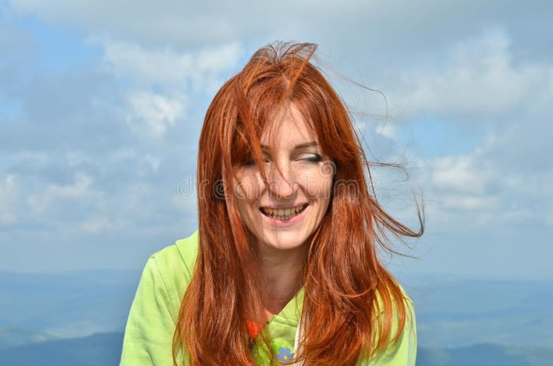 Den lyckliga skratta kvinnan med rött hör turist- i solljuset i bergen i himmelbakgrund, vind rufsar hennes hår royaltyfri fotografi