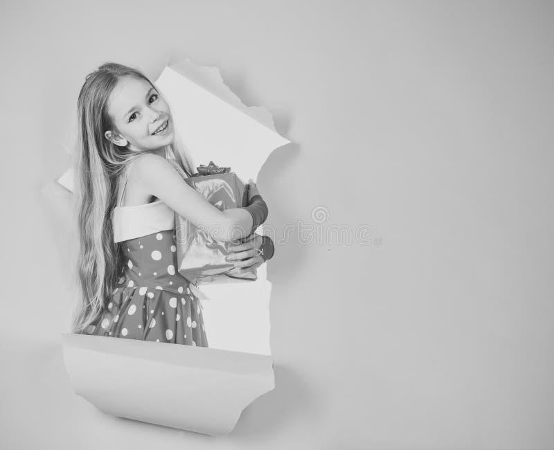 Den lyckliga skratta lilla flickan, förtjusande litet barn i en färgrik partiklänning och att rymma många födelsedaggåvor som öpp fotografering för bildbyråer