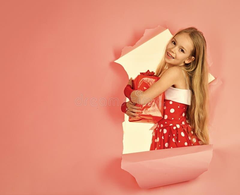 Den lyckliga skratta lilla flickan, förtjusande litet barn i en färgrik partiklänning och att rymma många födelsedaggåvor som öpp arkivfoto