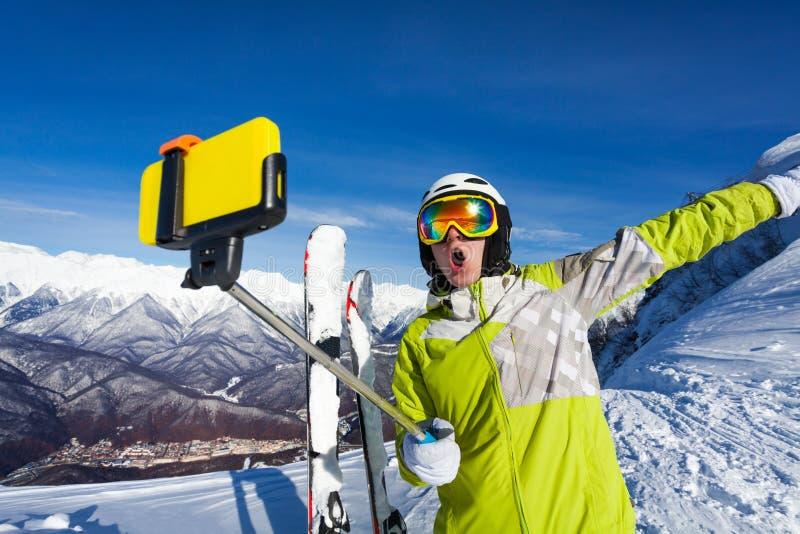 Den lyckliga skrikiga skidåkaren tar fotoet med kameran fotografering för bildbyråer