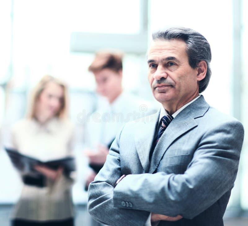 Den lyckliga smarta aff?rsmannen med laget parar ihop att diskutera i bakgrunden i kontoret arkivfoton