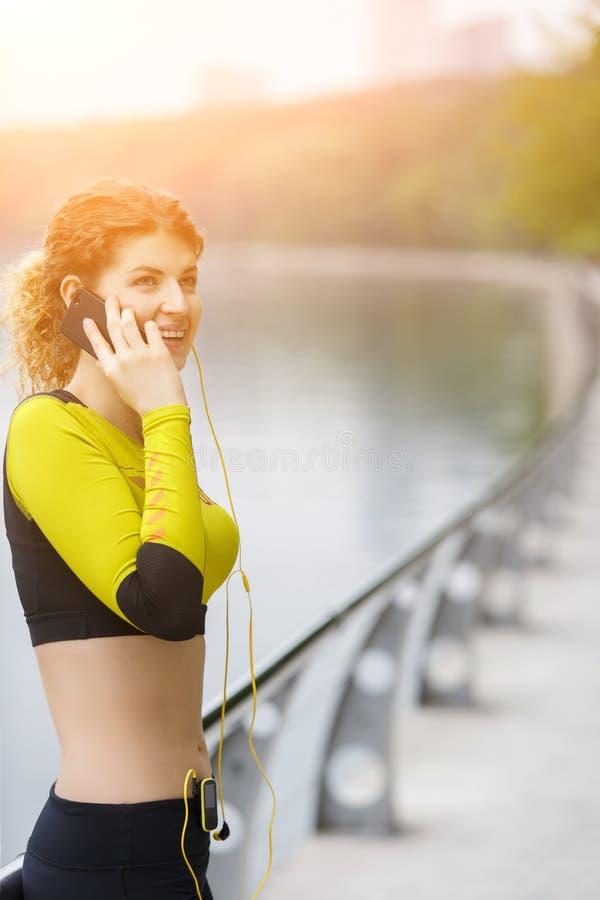 Den lyckliga sportiga flickan som talar på telefonen parkerar in arkivbild