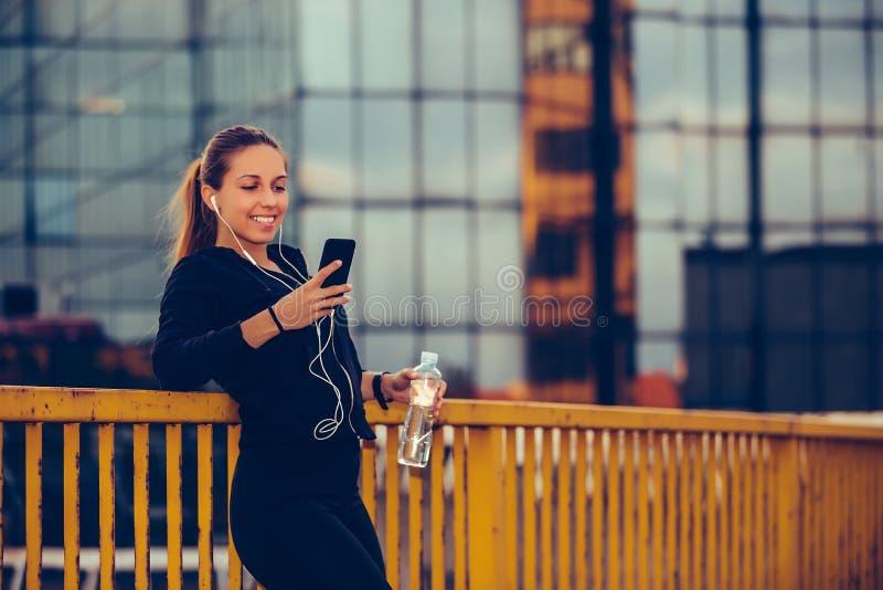 Den lyckliga sportiga flickan som tar ett avbrott efter, utarbetar och lyssnande musik, medan genom att använda den smarta telefo royaltyfri fotografi