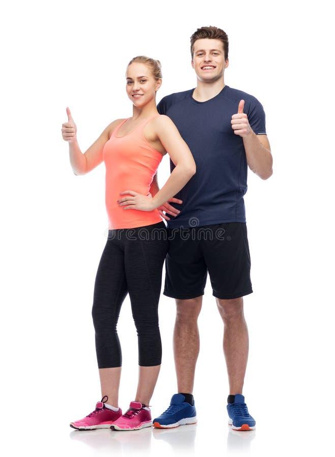 Den lyckliga sportive man- och kvinnavisningen tummar upp royaltyfri bild
