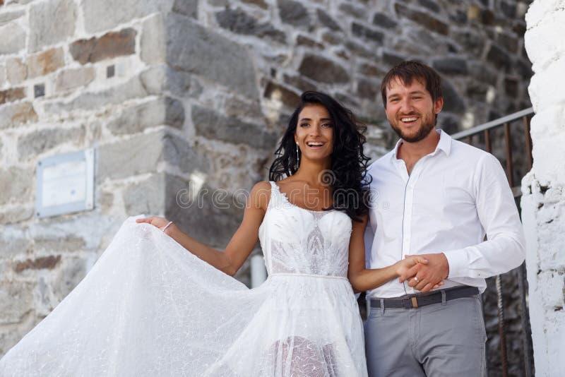 Den lyckliga ståenden av nygifta personer för ett par poserar att omfamna tillsammans nära den gamla gråa väggen i Grekland kopie arkivfoto