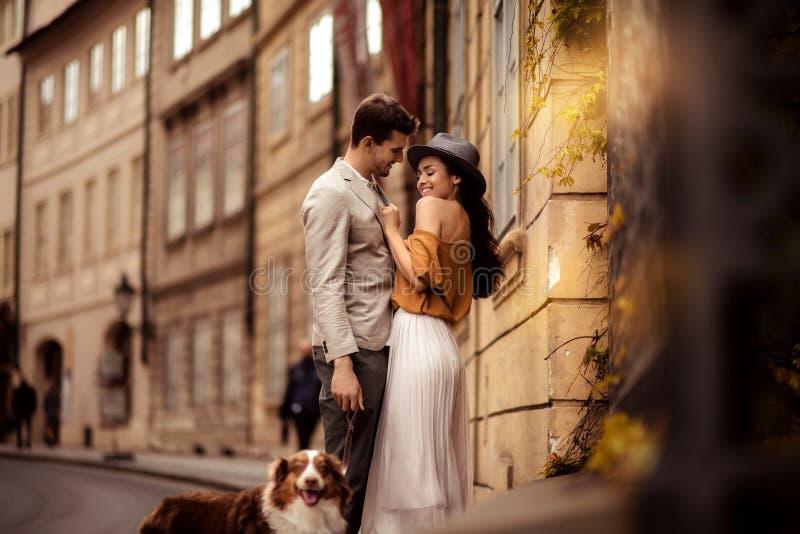 Den lyckliga stilfulla mannen strosar med hunden, omfamnar hans härliga eleganta flickvän, har bra förhållande och känner riktig  royaltyfri foto