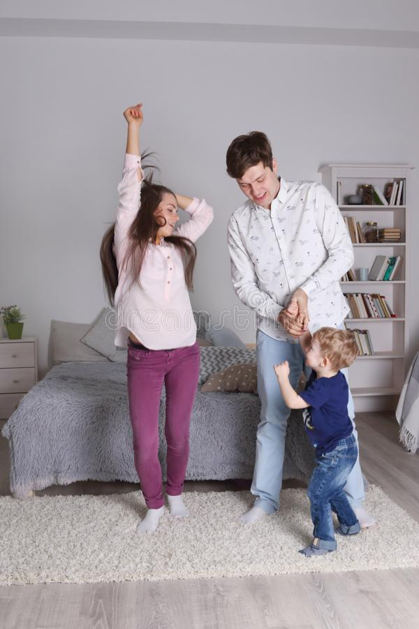 Den lyckliga stiliga fadern, modern och den lilla sonen dansar fotografering för bildbyråer
