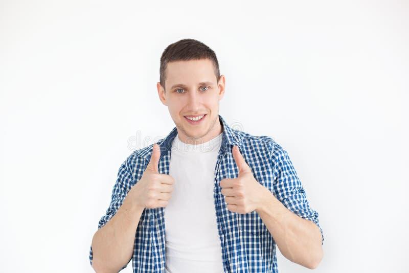 Den lyckliga stiliga manvisningen tummar upp En stilfull man i en skjorta har en le blick, annonserar en produkt Folk som annonse arkivfoton