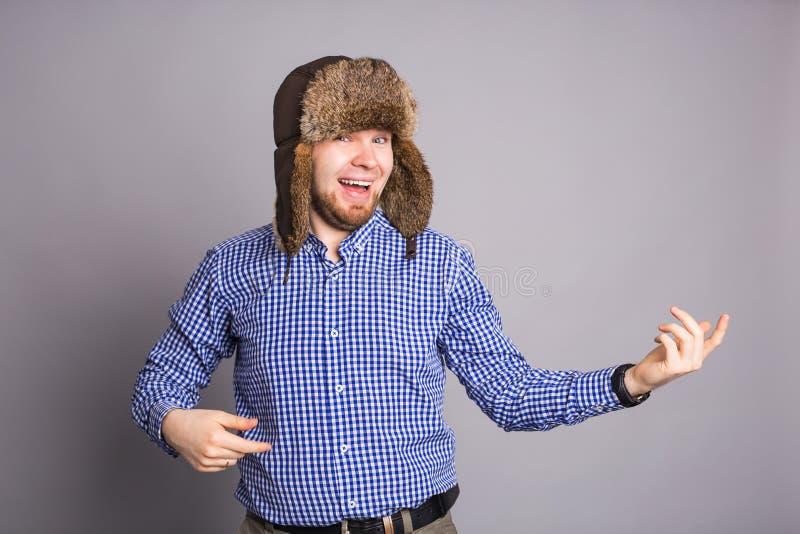 Den lyckliga stiliga unga mannen i lock med earflaps ler i studio royaltyfri foto