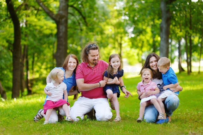 Den lyckliga stora familjen som har gyckel i sommar, parkerar royaltyfria foton