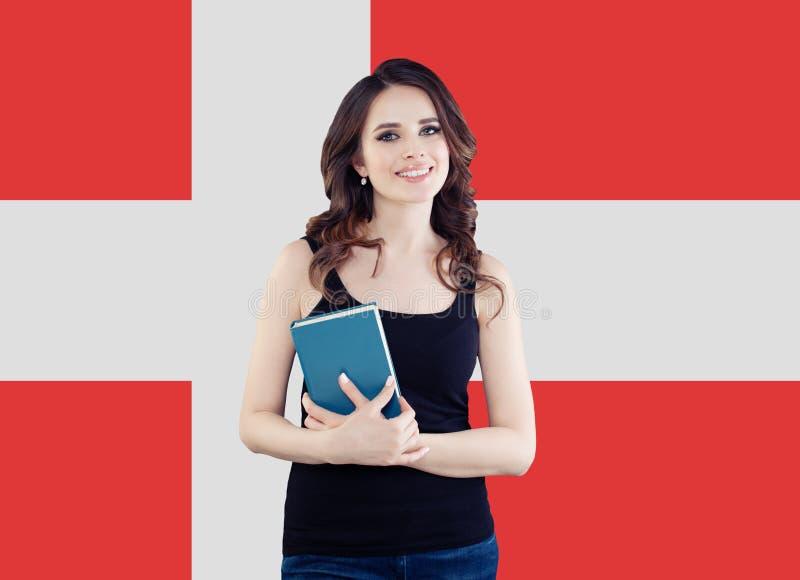 Den lyckliga studenten för den unga kvinnan med boken mot den Danmark flaggabakgrunden, reser och lär danskt språkbegrepp royaltyfria bilder