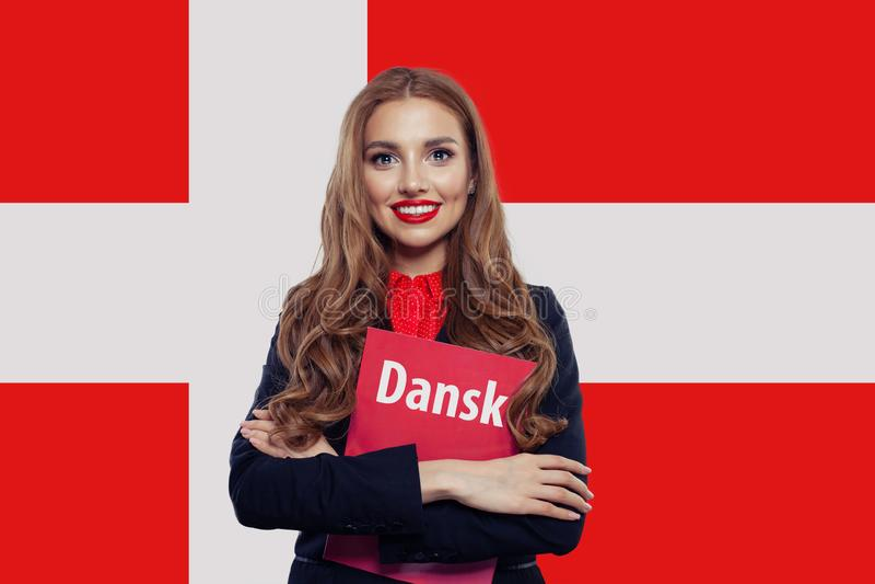 Den lyckliga studenten f?r den unga kvinnan med boken mot den Danmark flaggabakgrunden, reser och l?r danskt spr?kbegrepp royaltyfri foto