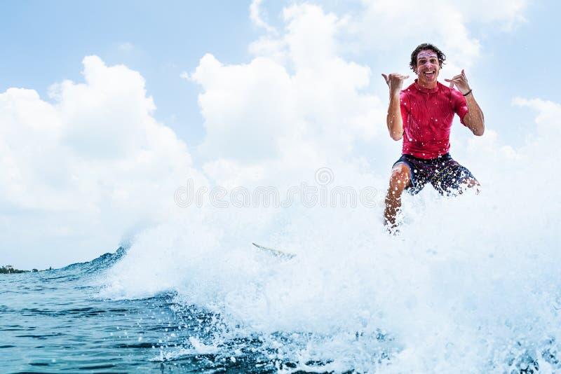 Den lyckliga surfaren rider vågen royaltyfria foton