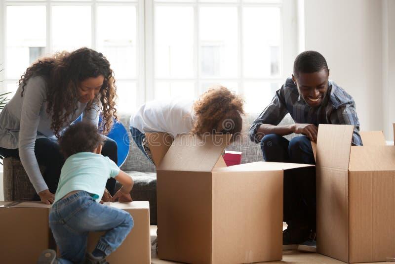 Den lyckliga svarta familjen med små ungar packar upp askar royaltyfria bilder