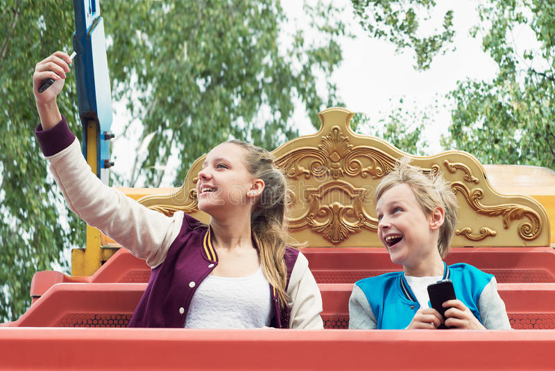 Den lyckliga tonåret rider på karusellen och gör selfie fotografering för bildbyråer