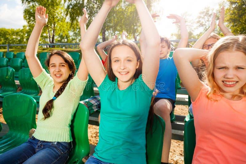 Den lyckliga tonåret rymmer armar upp under leken på tribun royaltyfri fotografi
