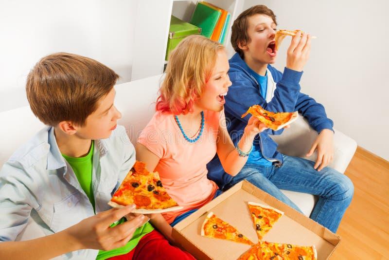 Den lyckliga tonåret som äter pizza, lappar tillsammans hemma royaltyfri fotografi