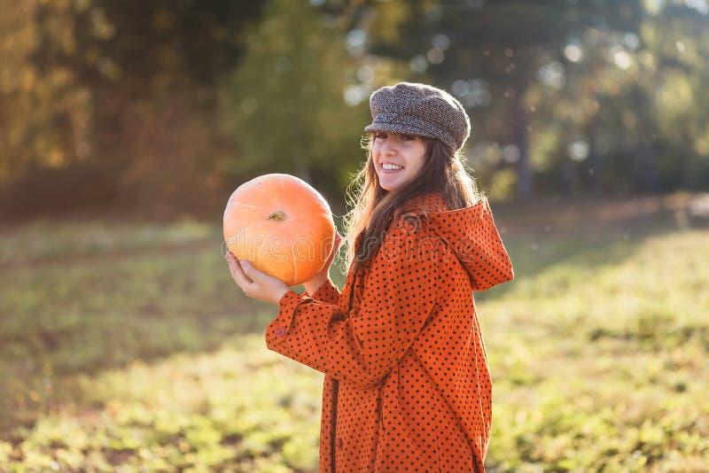 Den lyckliga tonåriga flickan bär en orange pumpa i henne händer royaltyfri foto