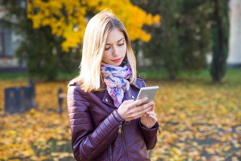 Den lyckliga tonåriga flickan med telefonleende under att gå på höst parkerar Nedgångbegrepp royaltyfria bilder