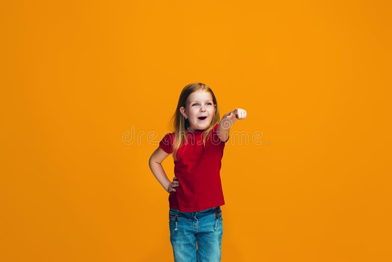 Den lyckliga tonåriga flickan som pekar till dig, halv längdcloseupstående på orange bakgrund arkivfoton