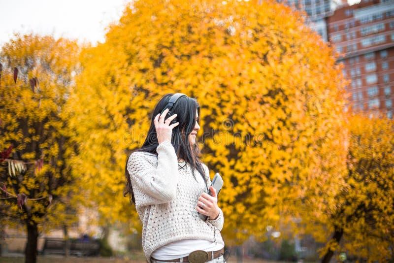 Den lyckliga tonåriga kvinnan som lyssnar till musik och, kopplar av i höst parkerar Gula träd, härlig nedgångtid royaltyfria bilder
