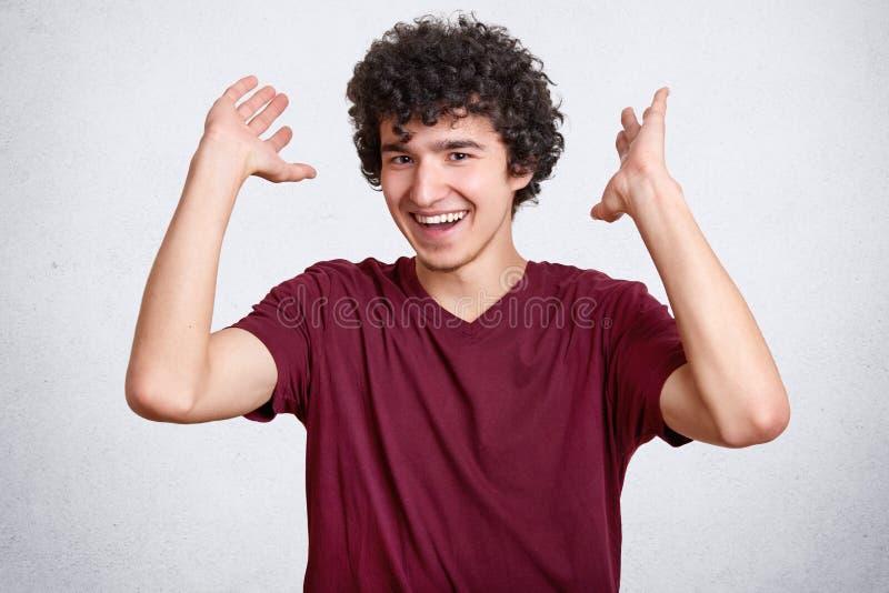 Den lyckliga tonåringen med lockigt hår, den iklädda tillfälliga t-skjortan, gester med händer, skratt på något, poserar mot vitb arkivbilder