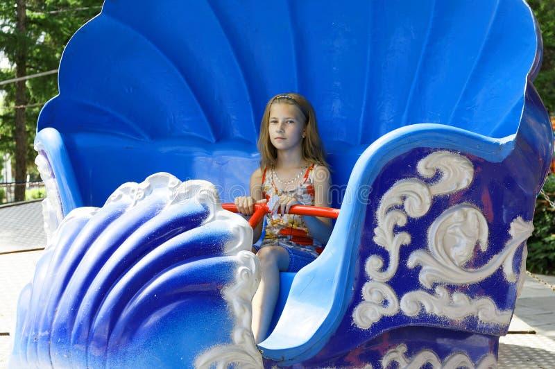 Den lyckliga tonårs- flickan rider på en gammal dragning royaltyfri foto