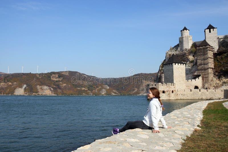 Den lyckliga tonårs- flickan sitter vid den flodGolubac fästningen royaltyfria foton