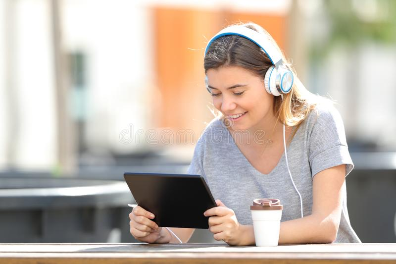 Den lyckliga tonårs- flickan som lyssnar till musik som använder minnestavlan i, parkerar arkivbild