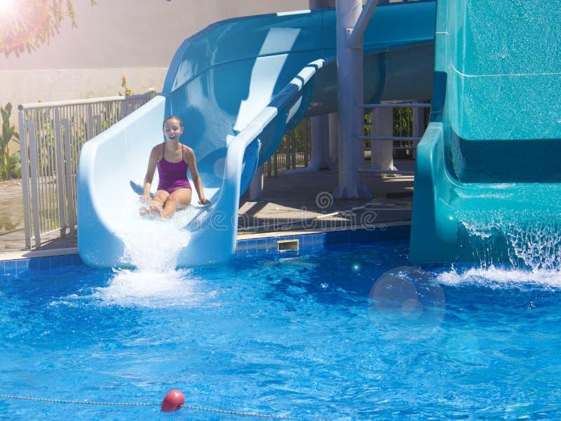 Den lyckliga tonårs- flickan som ner går förbi vatten, glider in i pölen royaltyfri bild
