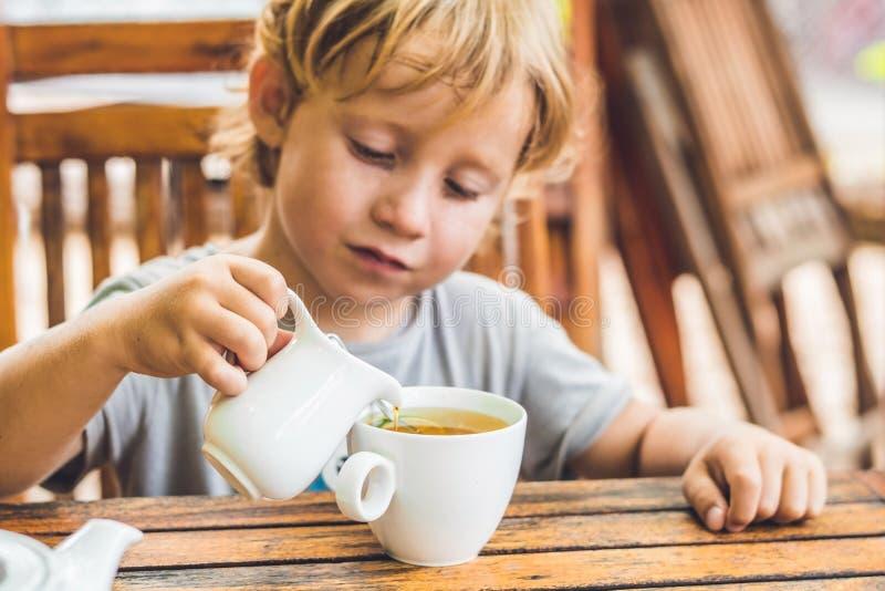 Den lyckliga trevliga pojken häller honung in i teet i sommargräsplanträdgård Stående utomhus- royaltyfri foto