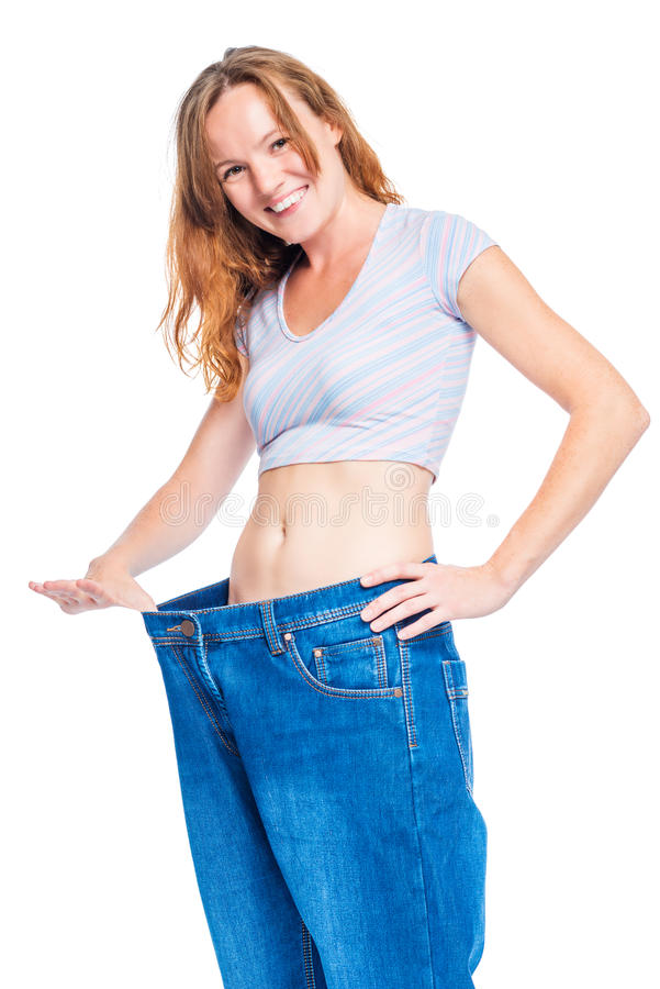 Den lyckliga tunna kvinnan i stor jeans ler mot en vit royaltyfri fotografi