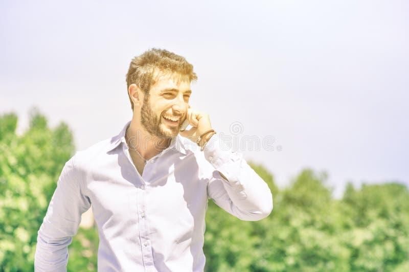 Den lyckliga unga affärsmannen på parkerar med smartphonen som har ett avbrott arkivfoto