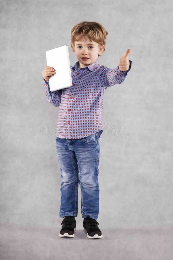 Den lyckliga unga affärsmannen visar upp tummen, minnestavlan i hand fotografering för bildbyråer