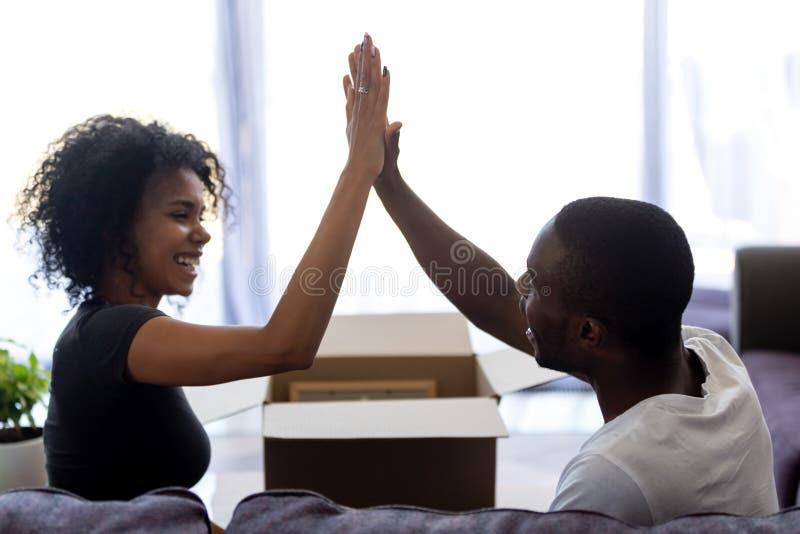 Den lyckliga unga afrikanen hyr par som ger fira flytta sig högt fem royaltyfri foto