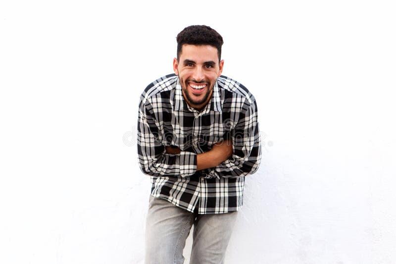 Den lyckliga unga arabiska mannen som skrattar med armar, korsade mot vit bakgrund fotografering för bildbyråer