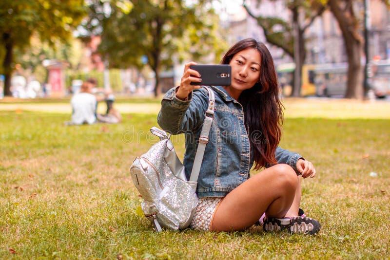 Den lyckliga unga asiatiska flickan med en telefon som tar en bild av henne i, parkerar royaltyfri foto