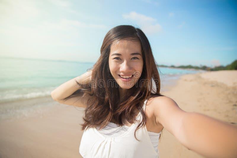 Den lyckliga unga asiatiska kvinnan tar foto, leende till kameran fotografering för bildbyråer